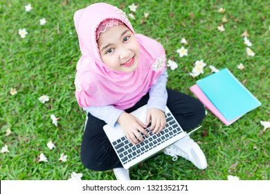 asian Islamic children do homework with laptop on green grass, Muslim children connect internet and search information, she feeling fun and smile, education time in the garden