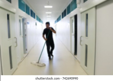 Asian janitor man mopping floor in office building or walkway school blur image use for background.