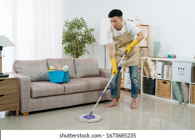 Asian japanese young man wearing apron cleaning floor at home. guy washing floor with mopping stick and bucket in living room of bright modern apartment. male household helping wife tidy house.