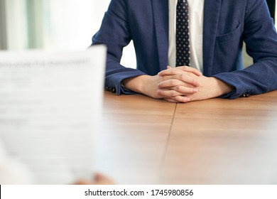 asian job seeker being interviewed by human resources manager in office, focus on hands of the candidate