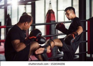Asian kickboxing player and him trainer in boxing gym, this photo can use for muay thai, sport, thai, combat and coach concept