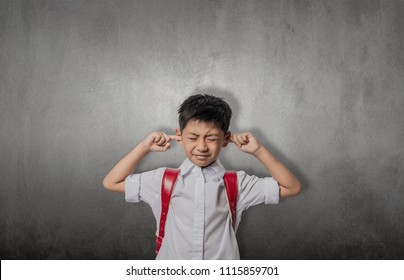 asian kid annoyed sticking fingers in ears with eyes closed, not listening to loud noise, ignoring stressful environment, stubborn teen refuses hearing, feels ear ache, tinnitus, concept idea.