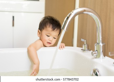 Asian kid in the bathroom with bathtub