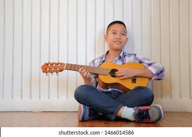 asian kid boy child playing guitar ukulele at home. children leisure activity