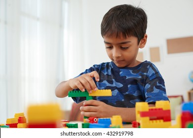 Asian kid building with plastic colorful bricks