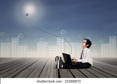 Asian kid with business clothing working on laptop. Background is scribble of cityscape