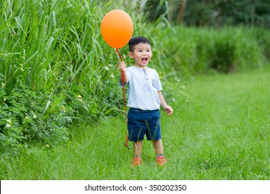 Asian kid catch up with his balloon