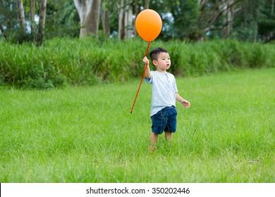 Asian kid catch with his orange ballon