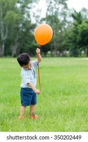 Asian kid catch with orange ballon