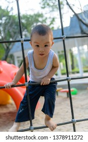 Asian kid climbing on the net in the park