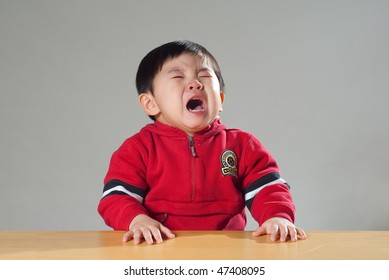 An Asian Kid, crying and looking sad