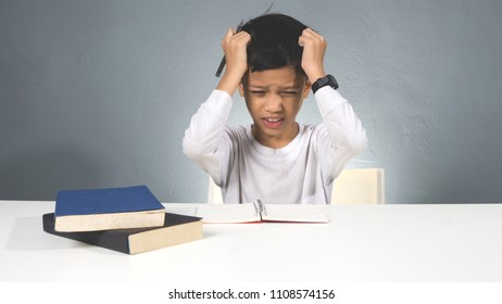 Asian kid doing homework at his study table with stress face action.Kid got problem with homework.Lazy kid at study table.
