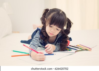 Asian kid drawing and do homework on the bed room, kid, child, studen, creative concep