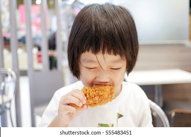 asian kid eating deep fried chicken