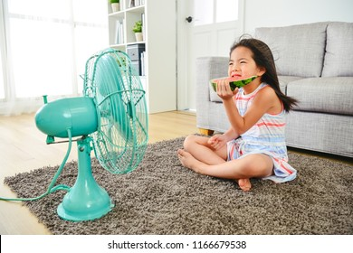asian kid feeling cold while sitting in front of fan.  eating a sliced watermelon on the ground. with a frowning face.