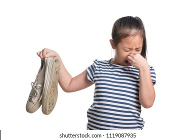 Asian kid girl age 7 year hold stinky shoe isolated on white background , Disgusted girl holding a smelly shoes