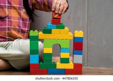 Asian kid girl building house from plastic blocks , banana plastic block on top