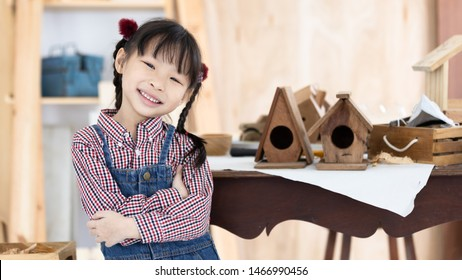 Asian kid girl carpenter working on woodworking table in home carpentry shop, Little asian kid girl works in home carpentry shop.