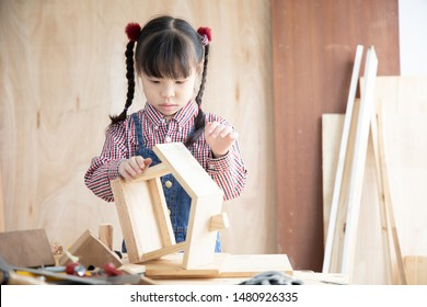 Asian kid girl carpenter working on woodworking table in home carpenter shop.