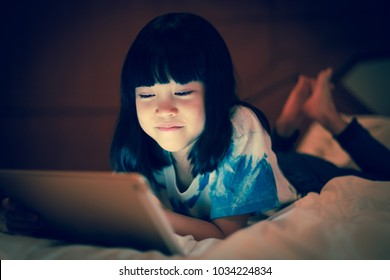 Asian kid girl enjoy using online internet for social communicate with friends while lying on the bed, in dim light bedroom background, screen light reflex on her face with cute smiling.