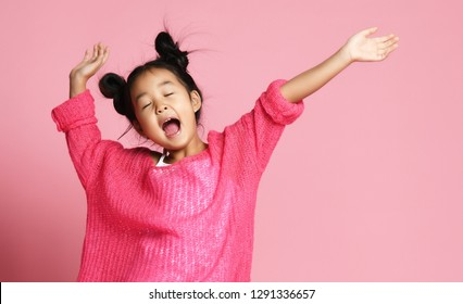 Asian kid girl in pink sweater, white pants and funny buns sings singing dancing on pink background