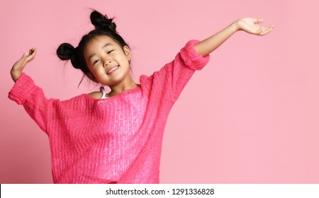 Asian kid girl in pink sweater, white pants and funny buns stands with hands up and smiles on pink background. close up