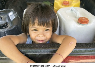 asian kid girl  sat in the pickup with fuel gallon