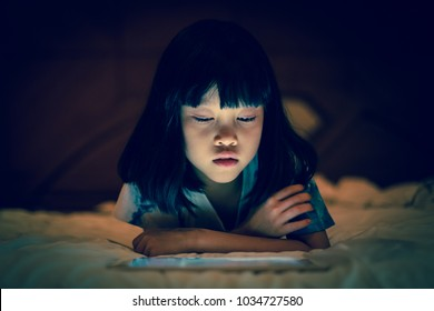 Asian kid girl using tablet watching movie while lying on bed, in dark background of bedroom, bright light screen reflex on her face.