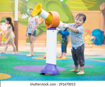 Asian kid having fun at water park during summer holiday. Boy playing with water gun