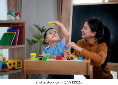 Asian kid and his teacher play doh togather in class room in preschool, this image can use for art, education, student and school concept