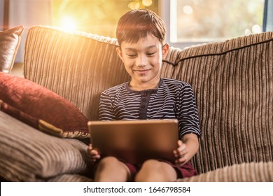 asian kid holding and playing on his ipad tablet device sitting on sofa with pillow, smiling joyfully enjoying free time, sunset jour with light shining in living room, wearing short and stripy shirt