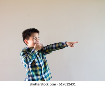 Asian kid laugh with hand close to the mouth and another hand point to something