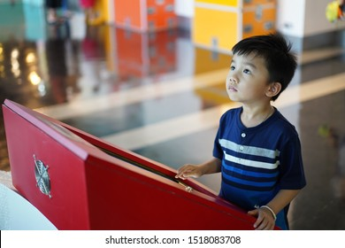ASIAN KID LEARNING FROM INTERECTIVE EXHIBIT