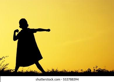 Asian kid ,Little child boy wearing a cape plays a super hero ,
