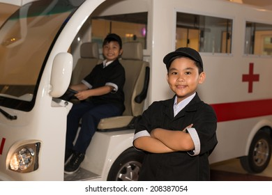 Asian kid in the medical service worker uniform posing in front of ambulance