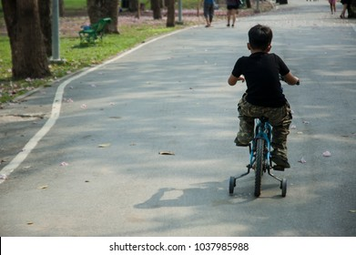 Asian kid model, boy, try to cycling in the park, 4 wheels bicycle, good healthy lifestyle, exercise everyday for good health, fit and firm, growth to smart and handsome man. Relax time with nature.