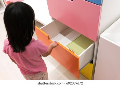 Asian kid open colorful drawer looking for some books.