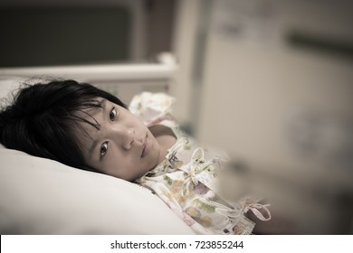 Asian kid patient child inpatient look at IV infusion drop on hospital bed.Medical healthcare concept.