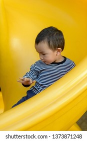 Asian kid playing on the slide in the park