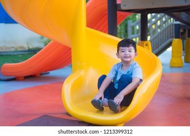 Asian kid playing slide at the playground under the sunlight in summer, Happy kid in kindergarten or preschool school yard.