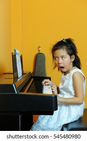 Asian kid practise piano in orange room