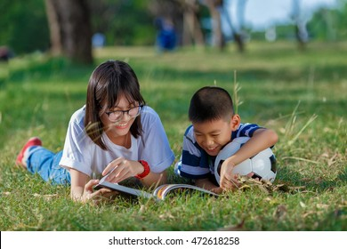 asian kid reading book in natural environment together