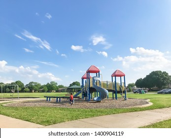 Asian kid running at colorful playground at public park in Texas, America. Cloud blue sky on green grass lawn