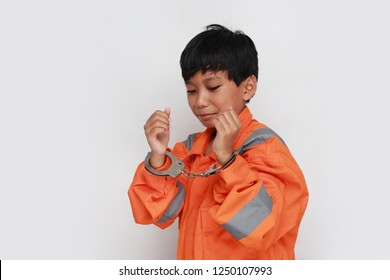 asian kid sad using handcuff. boy in handcuff.