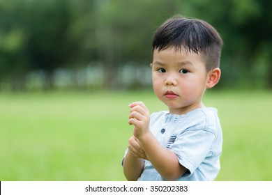 Asian kid scratching his arm