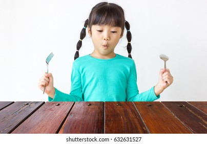 Asian kid with spoon and fork.