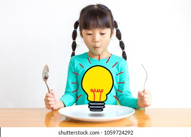 Asian kid with spoons and forks.She points to her plate of food. There are symbols of new ideas.