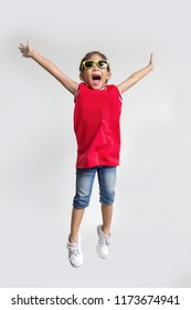 asian kid with sport shirt and sun glasses fashion jumping action on white background