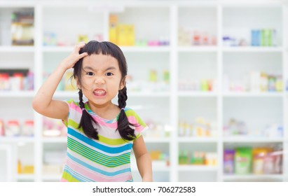 Asian kid is stressed, drug shelf in the pharmacy is the background.