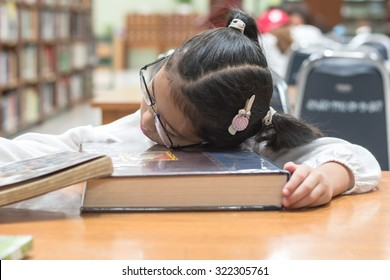 Asian kid student studying hard feeling tired in school library sleeping on big book in library or classroom